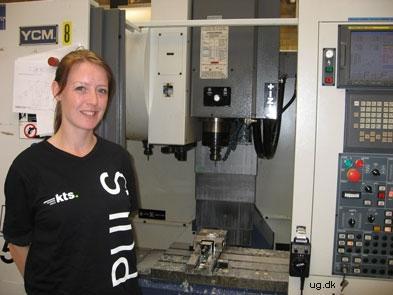 Foto af Scarlett foran en af maskinerne på skolen
