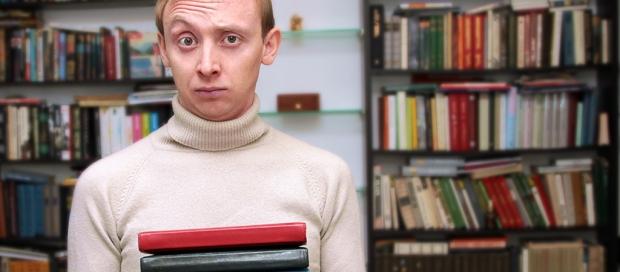 Ung mand med hævet øjnbryn og bøger i fanven