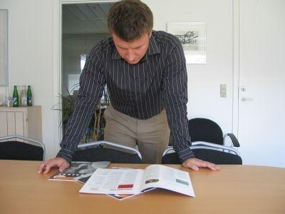 Foto af Thomas, der kigger i medarbejderblad