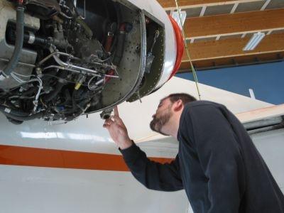 Foto af Anders, der undersøger en flymotor