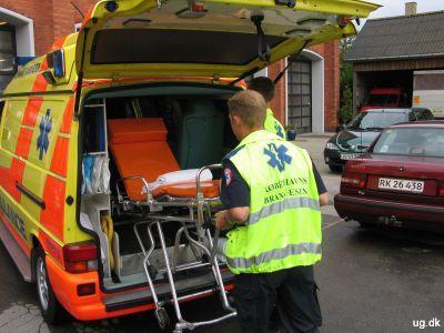 Foto af Thomnas og Mikkel, der lægger båren ind i ambulance