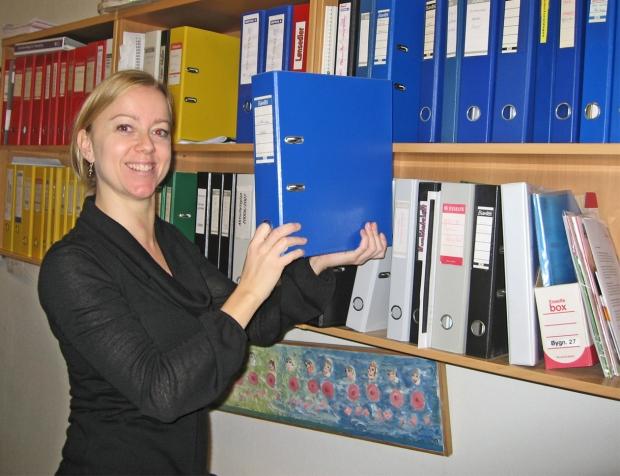 Foto af skolesekretæren med arkivmapper