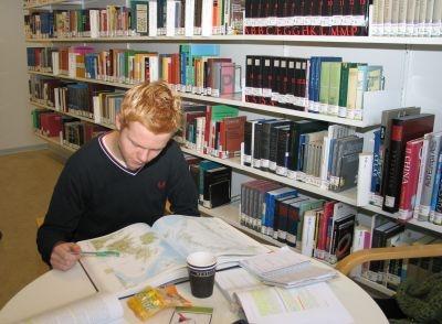 Foto af Thomas, der kigger i et atlas.