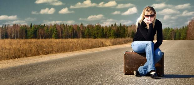 kvinde sidder på kuffert på vejen
