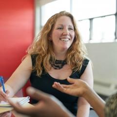 Smilende kvinde i samtale med kollega