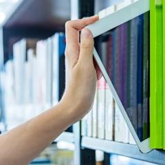 Hånd tager tablet ud af bogreol