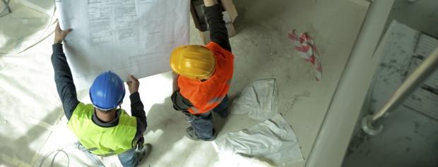 To håndværkere ser på byggetegning