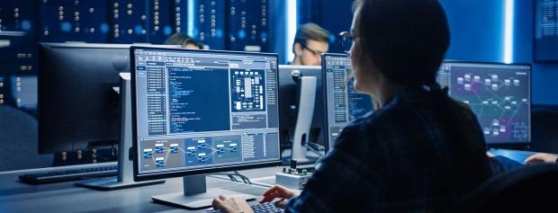 Tre medarbejdere sidder i et computerrum ved hver sin pc og overvåger data.