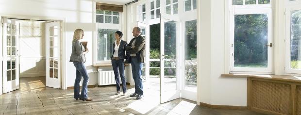 En ejendomsmægler viser et hus frem for køberne.