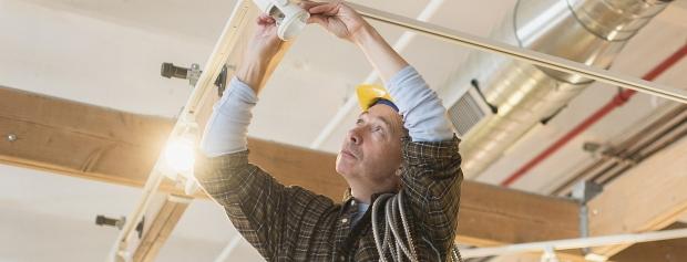 En elektriker sætter en lampe op