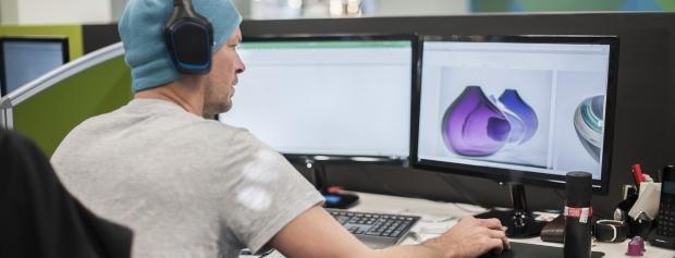 Ung mand med høretelefoner arbejder med foto på computer