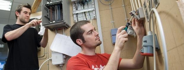 Elektrikerlærlinge monterer el-artikler