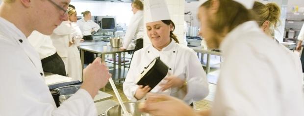 Kokkeelev i køkkenet sammen med kolleger