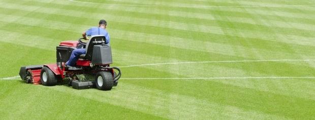 Greenkeeper slår græs på golfbane