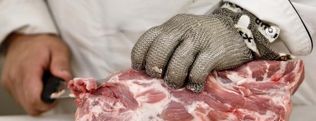 Nærbillede af industrislagters hænder med kniv og stålhandske