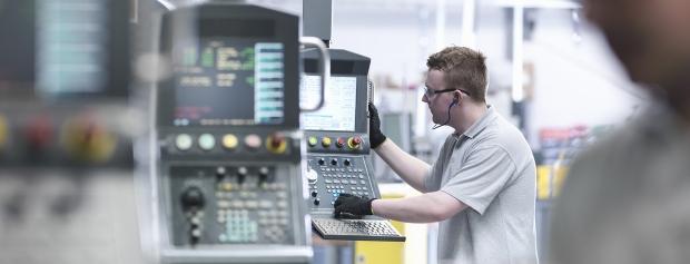Mand arbejder ved en CNC-maskine i en industrihal
