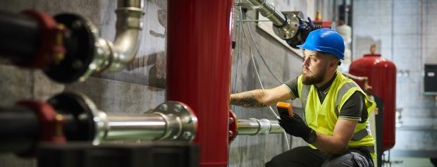 Mand inspicerer varmesystem i industrielt fyrrum