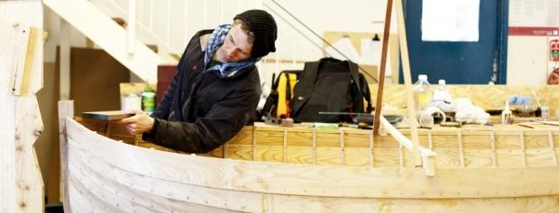 Bådebyggerelev arbejder med finish på en træbåd