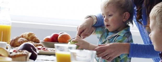 En pædagogisk assistentelev hjælper børn med at skære frugt