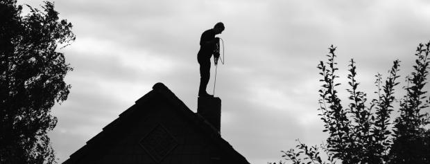 Skorstensfejerlærling på tagryg af hus