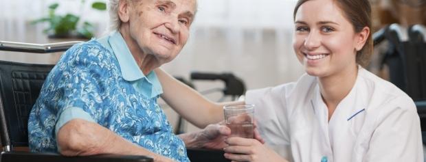 Sosuelev hjælper plejehjemsbeboer med at drikke