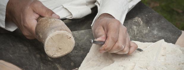Nærbillede af stenhugger med hammer og mejsel