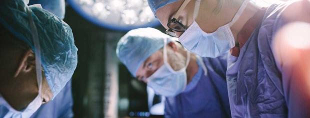En gruppe af kirurger står sammen og opererer en patient.