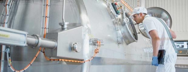 En mejeritekniker står og tjekker produktionen på en ostefabrik.