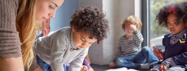 Pædagog sidder på gulvet og tegner sammen med nogle børn.