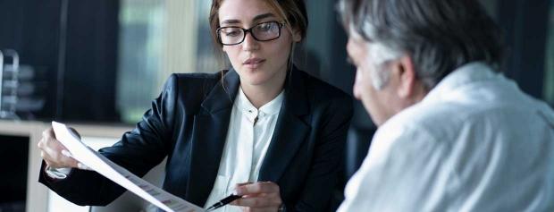 En revisor sidder ved skrivebordet og rådgiver en kunde.