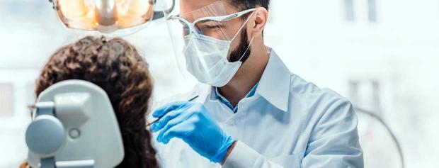 En tandlæge er i gang med at undersøge en patient.