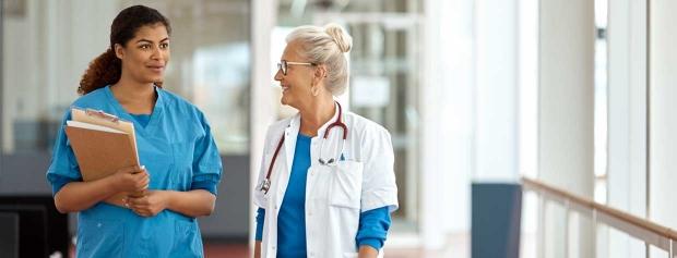 En sygeplejerske og en læge går på hospitalsgangen og taler sammen.