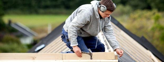 En tømrer er i gang med at lægge tag på et hus.